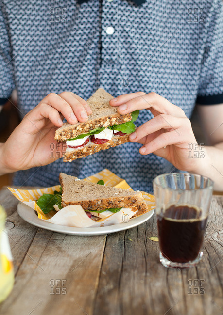 Man sitting down to eat a sandwich served with a glass of black coffee