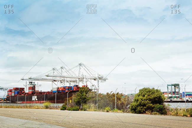 Oakland, CA - May 4, 2014: Shipping containers being loaded onto a cargo ship