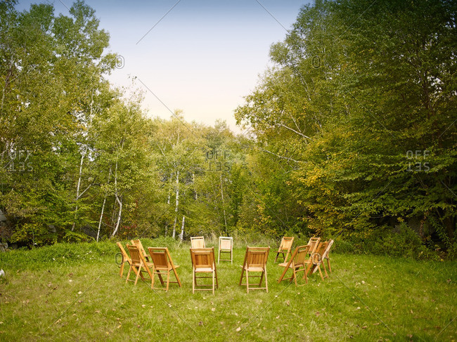 Wooden chairs arranged in a circle outdoors
