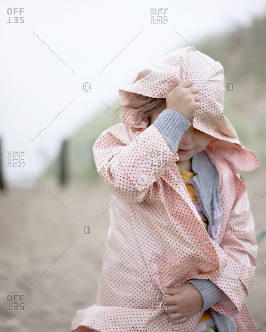 Young girl pulling raincoat over her head on beach