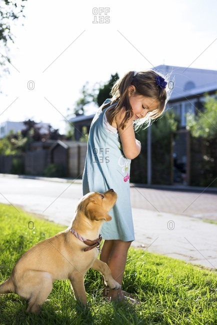 Young girl playing with her puppy
