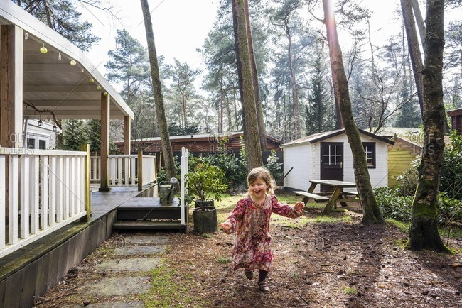 Young girl running outside cottage