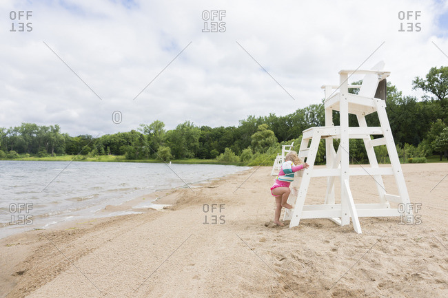 Toddler girl at beach climbing up lifeguard stand