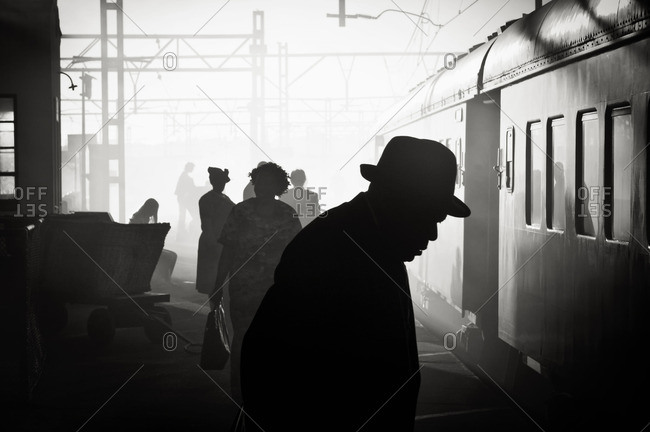 Silhouetted passengers at a train station