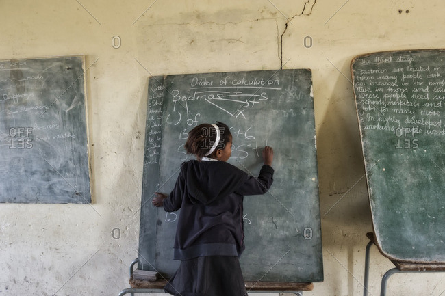 - July 30, 2010: Young girl writing on chalkboard in African classroom