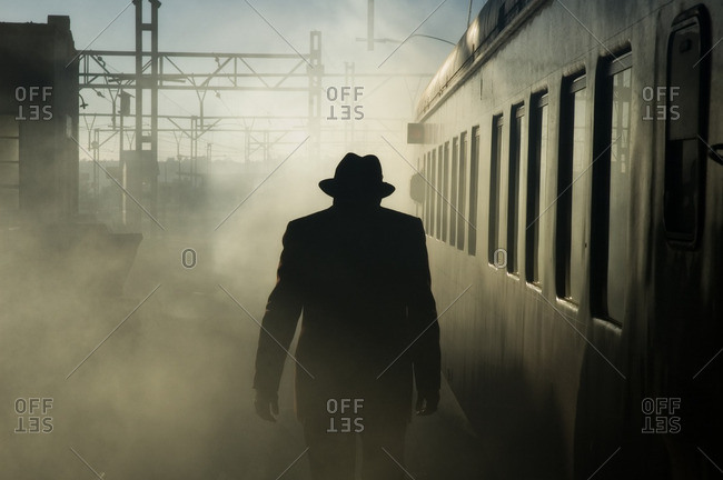 Man in hat silhouetted at train station