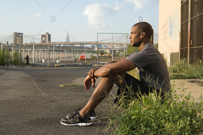 Runner sitting on street in Brooklyn