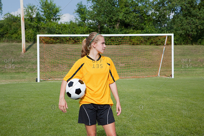 Girl soccer player posing with ball