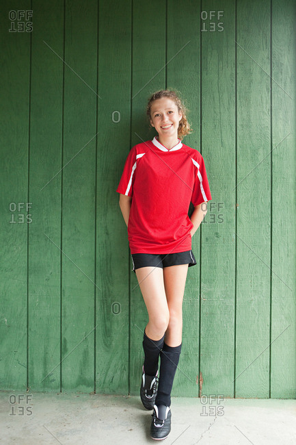 Girl soccer player with curly hair posing against a green wall