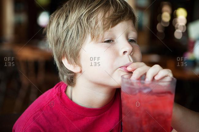 Boy drinking red soft drink