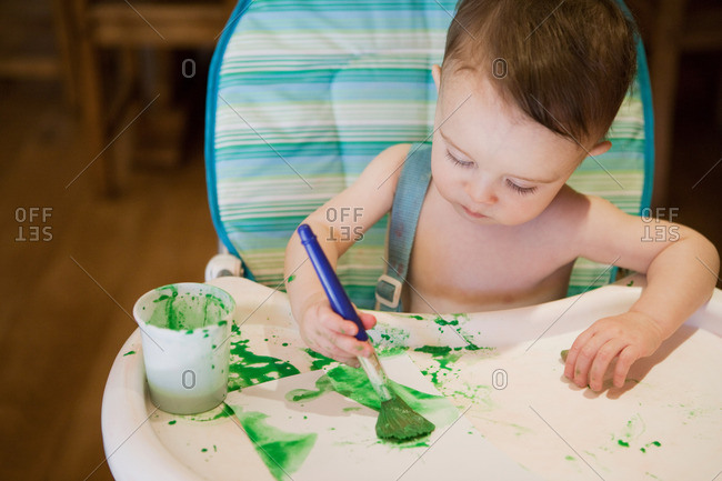 Baby boy sitting in high chair painting picture