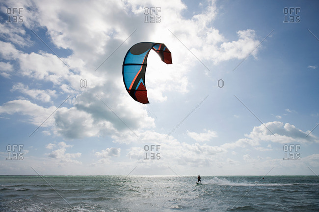 Young man kite surfing on partially cloudy day