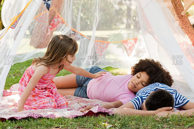 Three friends napping in summer netting tent