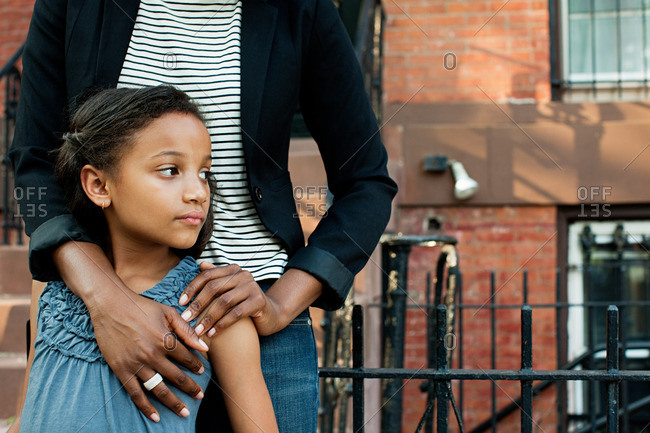 African American girl standing with mother, looking away