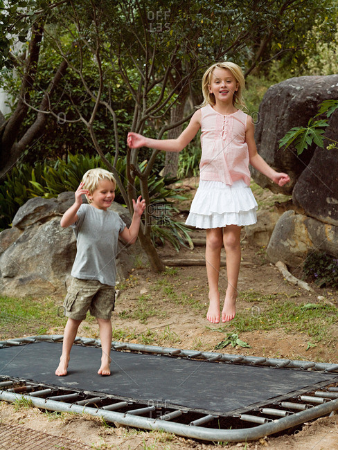 Brother and sister bouncing on trampoline