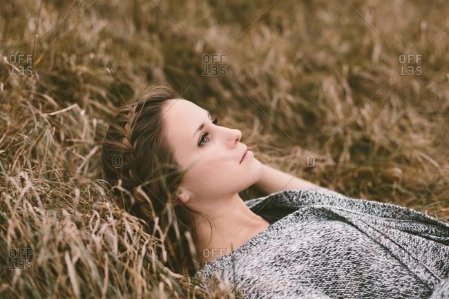 Woman lying in field of grass