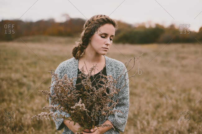 Woman in field with dry wildflowers