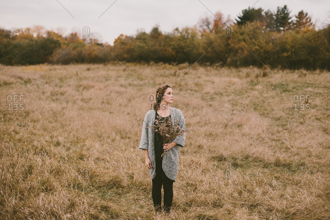 Woman in field with dry flowers