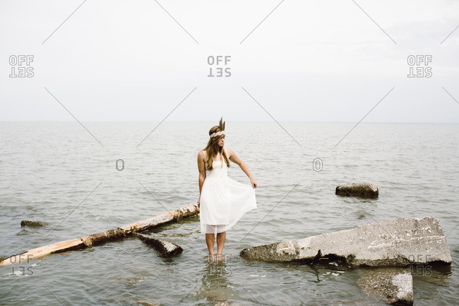 Woman holding dress in water