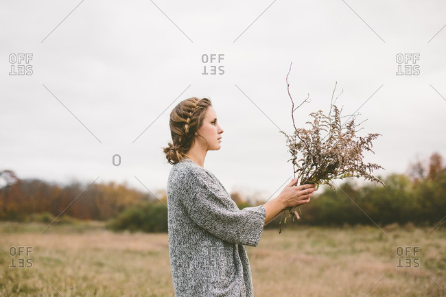 Woman holding dry flowers in field