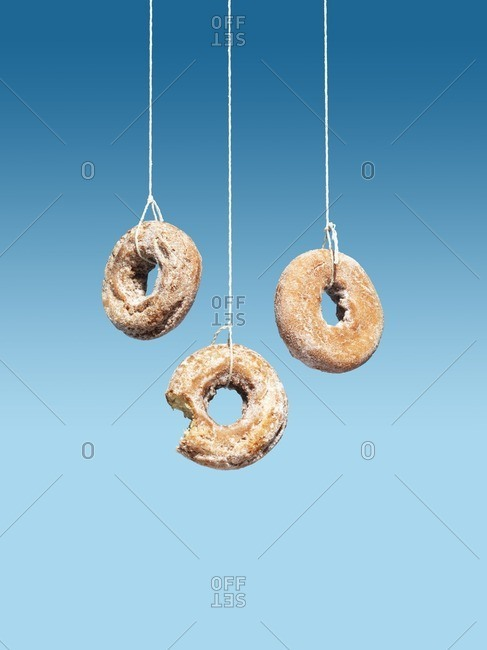 Donuts hanging from thread