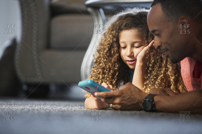 Father and daughter playing handheld game while lying on carpet at home