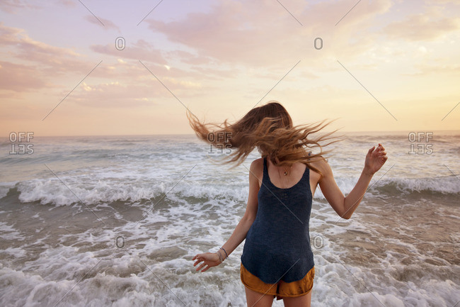 Woman tossing hair while standing at beach