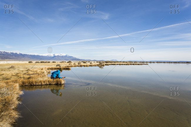 A young woman in a blue coat crouches to look into a shallow hot spring pond in a vast, dry landscape