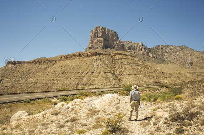 An older man in a wide brim hat stands at a desert overlook with a view toward a tall desert cliff