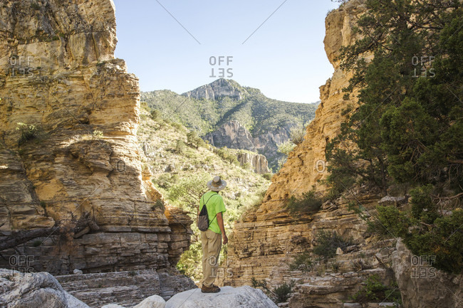 A man in hiking clothes stands on a rock outcrop looking through a V-shaped slot in a desert canyon