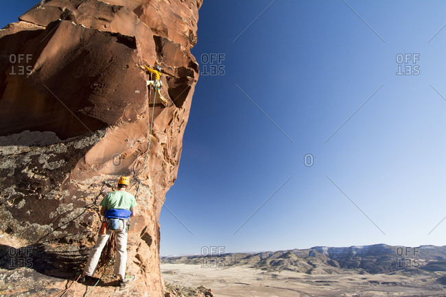 A man and woman rock  climbing a route on Psycho Tower above the Big Gypsum Valley, Naturita, Colorado