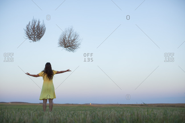 Woman in a yellow dress holding two tumbleweeds for no reason in the middle of North Dakota