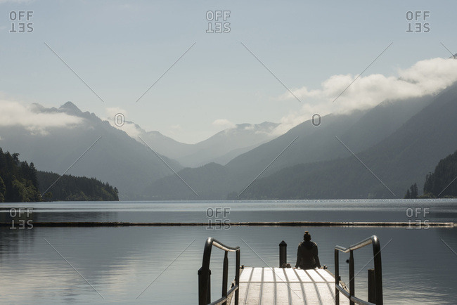 A woman sits on the end of a dock overlooking Lake Crescent in Olympic National Park, Washington