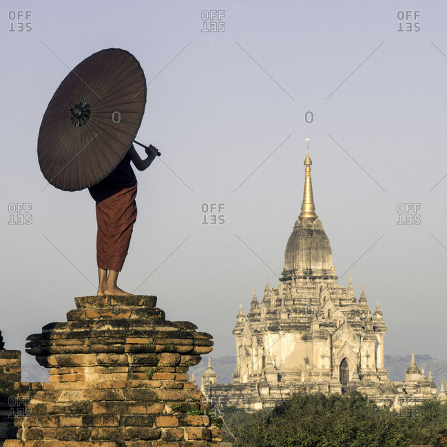Young Buddhist monk standing on temple top holding a parasol in front of an ancient temple
