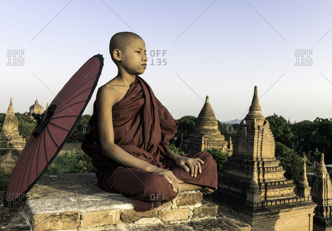Young novice Buddhist monk sitting on a temple top with a  parasol