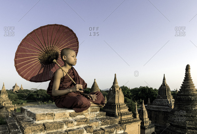 Young Buddhist monk sitting on a temple top holding a parasol