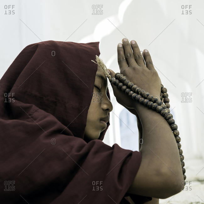 Young novice Buddhist monk praying inside temple corridor, with prayer beads