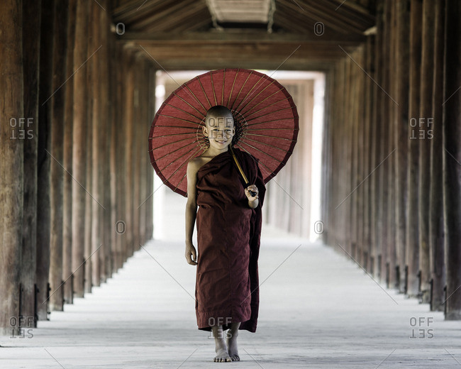 Young Buddhist monk walking along a temple complex corridor with parasol