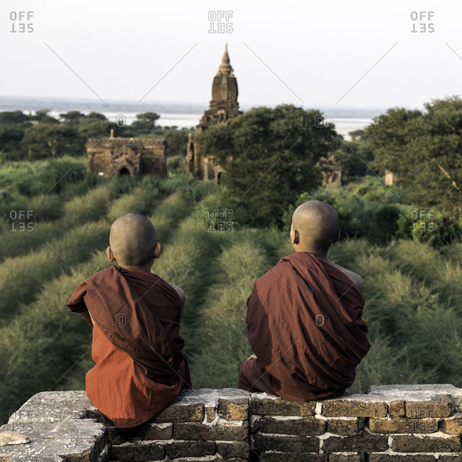 Young novice Buddhist monks sitting on a temple top looking out over ancient temple ruins