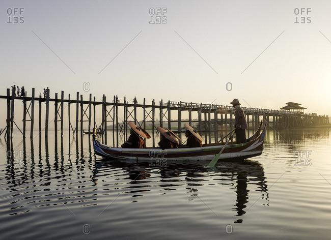 Buddhist monks taking a boat tour around Ubein Bridge