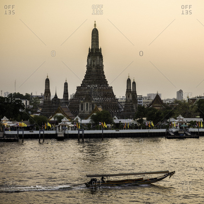 A passing longtail boat on the Chao Phraya river near Wat Arun at sunset