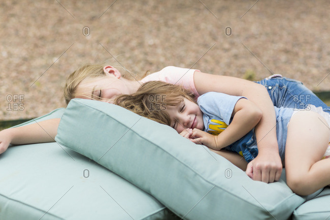 Children resting outside on a pile of cushions