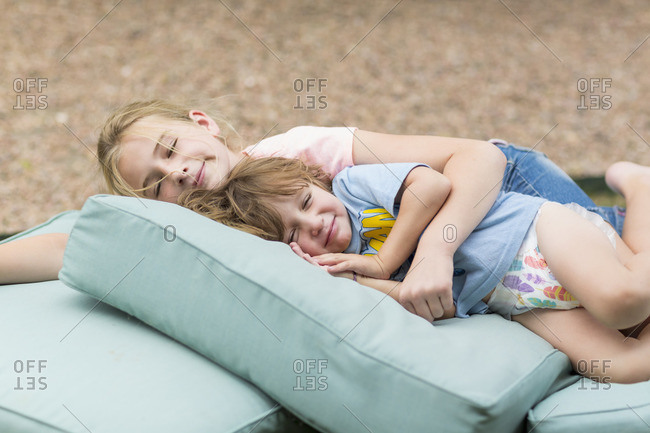 Children napping outside on a pile of cushions