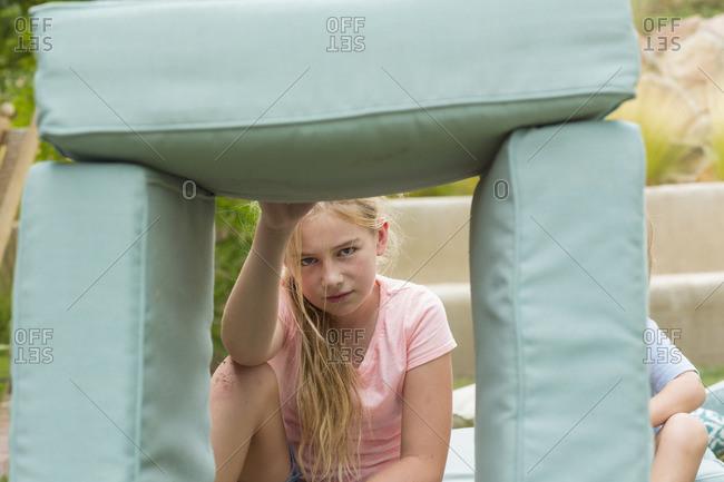Children building an outdoor fort with cushions
