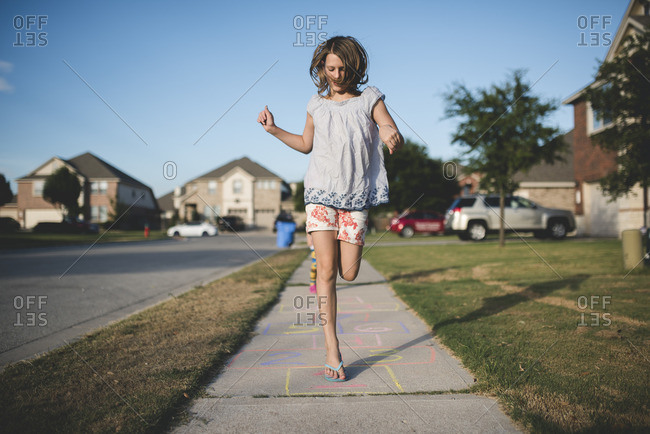 Girl jumping playing hopscotch