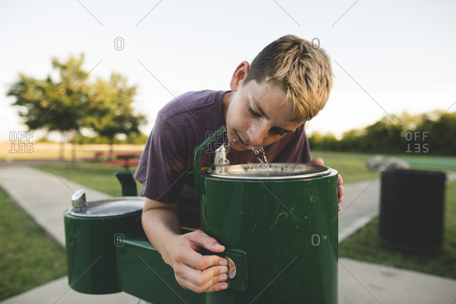 Boy at park drinking fountain