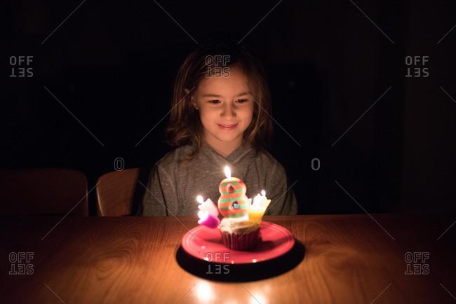 Girl celebrating her 8th birthday with a birthday cupcake