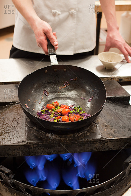 Male chef frying with wok in commercial kitchen
