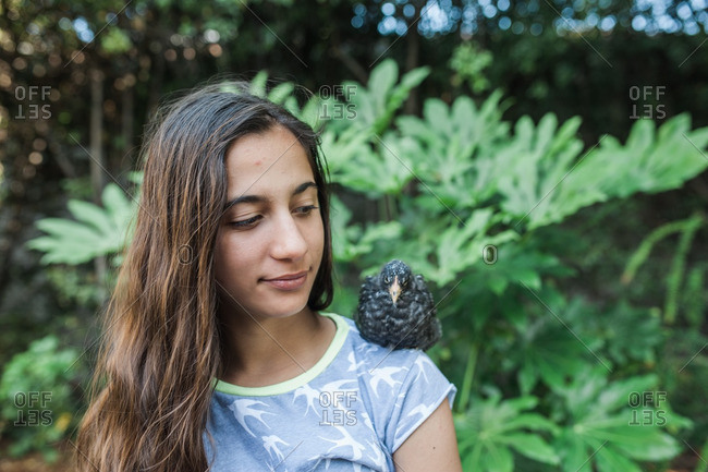 Teenage girl with a bird resting on her shoulder