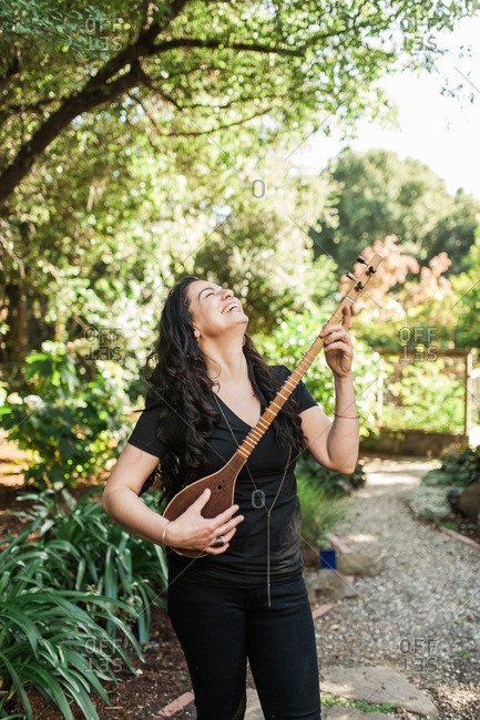 Woman holding a stringed instrument and laughing